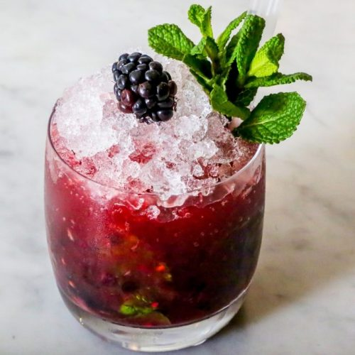 The Black Berry Beast, a signature cocktail with fresh berry, mint and licorice flavours, using Absinthe and Chambord forest berry liquor.